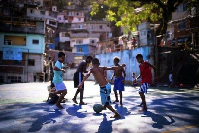 Мальчишки играют в футбол на улице