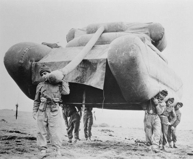 1954г Британские солдаты поднимают надувной муляж танка во время учений на равнине Солсбери