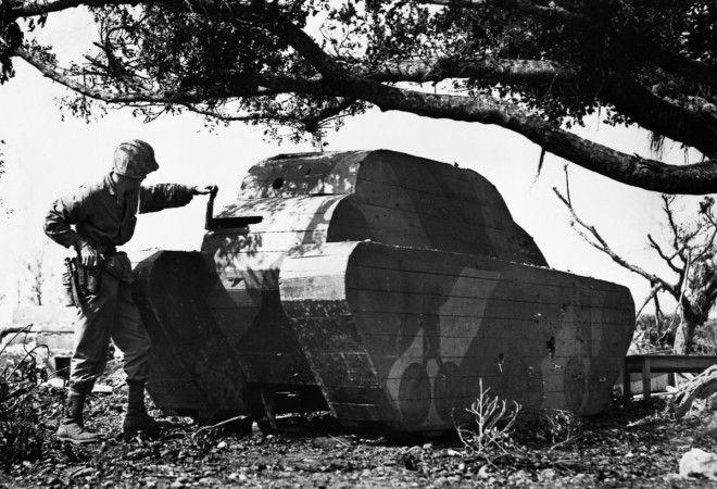 1945г Морской пехотинец армии США осматривает деревянную планку в муляже японского танка на Окинаве