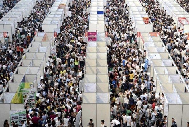 Тысячи лиц ищущих работу рассматривают стенды на ярмарке вакансий в городе Чунцин