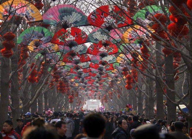 Толпы людей ходят среди деревьев украшенных красными фонарями на храмовой ярмарке в честь празднования китайского Нового года в Пекине
