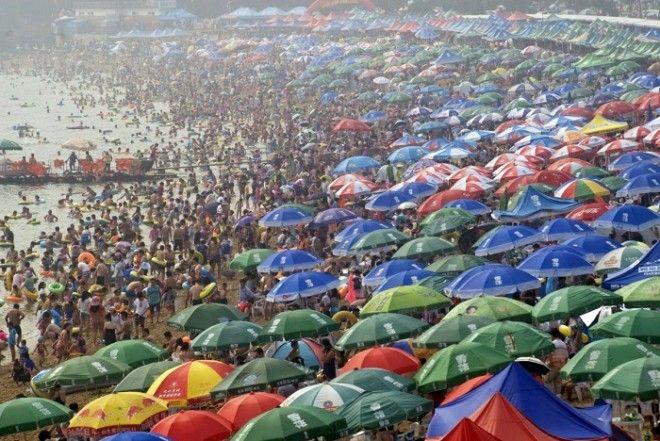 Люди толпятся на пляже в городе Далянь провинция Ляонин спасаясь от летней жары