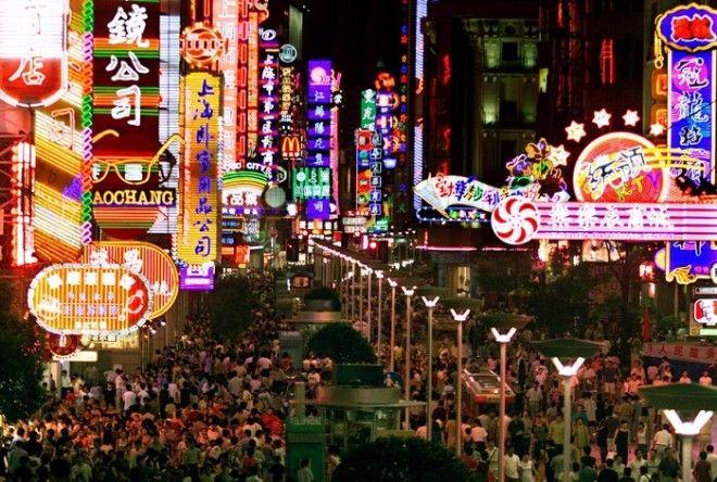 Покупатели толпятся под красочными неоновыми огнями вдоль оживленной Нанкинской улицы Шанхая