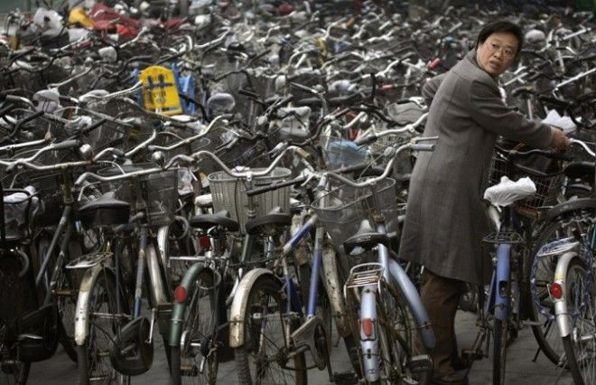 Женщина забирает свой велосипед на стоянке за станцией метро в Пекине
