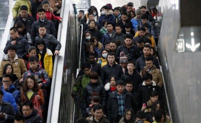 Люди спускаются на эскалаторе и сходят по лестнице направляясь к платформе метро в час пик в Пекине