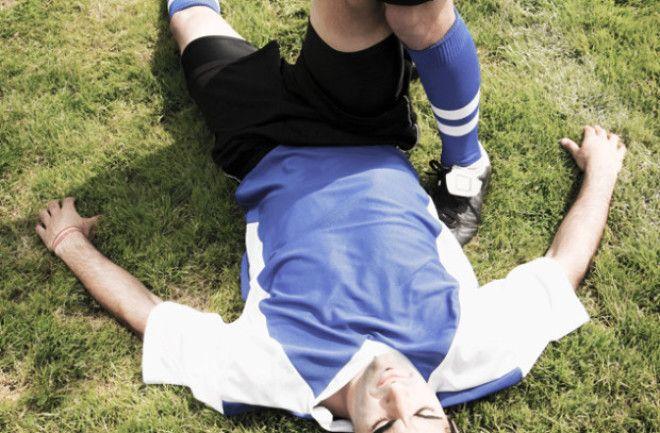 Футболист лежащий на газоне