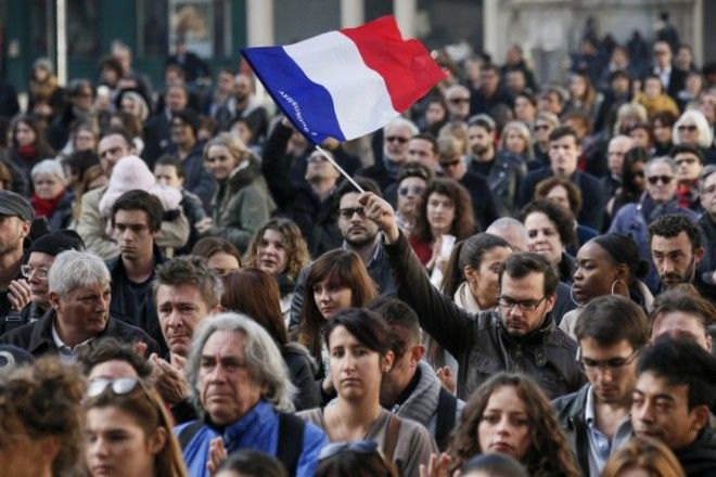 A man waves a French flag as several hundred people gather to observe a minute of silence in Lyon France November 16 2015 to pay tribute to the victims of the series of deadly attacks in Paris on Friday REUTERSRobert Pratta