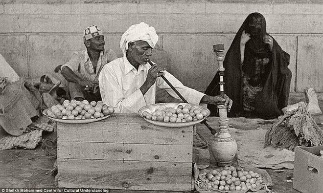 Мужчина, продающий приправы и лимоны, курит кальян, 1960-е